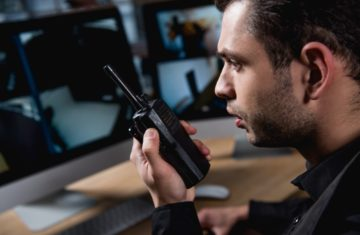 selective focus of guard holding walkie-talkie at workspace